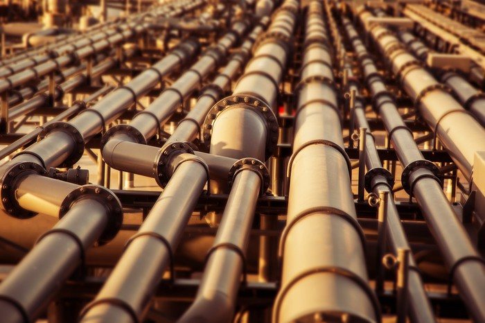 A row of oil and gas pipelines stretching into the distance.