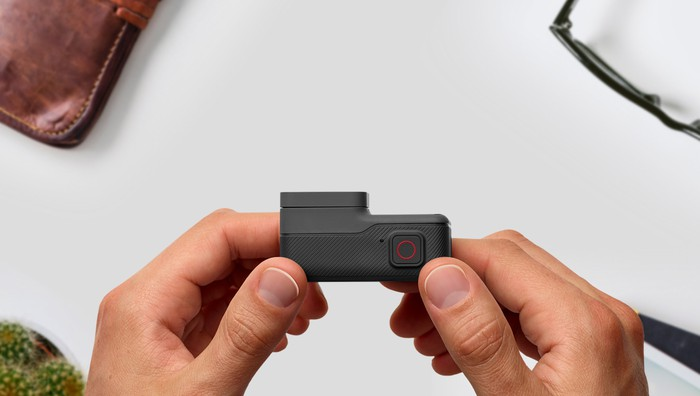 View from above of two hands holding a GoPro HERO5 camera, with a wallet and glasses on a table below