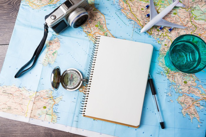 Map with various travel items on top, including a camera, pen, notebook, toy plane, and compass