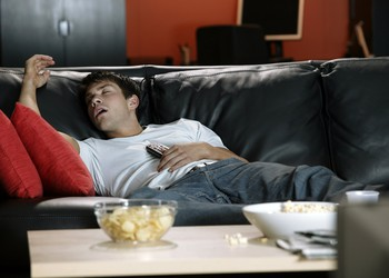 Man sleeping on couch with TV remote