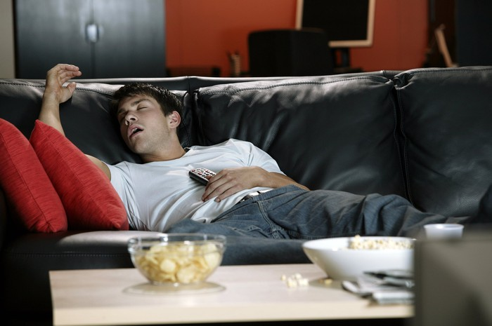 Young man sprawled on a couch with eyes closed and open mouth, holding a TV remote against his chest.