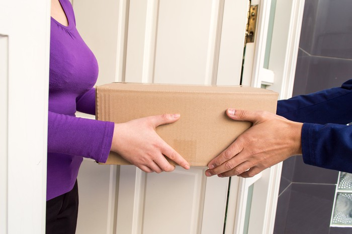 Woman accepting a cardboard-box package from a courier at the door