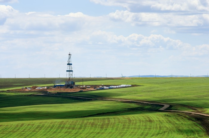 A drilling rig rises up against the sky and swaths of green fields.