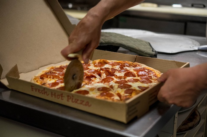 A hand holding a pizza cutter slices into a pizza, while another hand holds the cardboard box it's contained in.