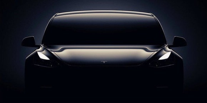 A teaser image for the Tesla Model 3, with a front view of the vehicle shrouded in darkness.