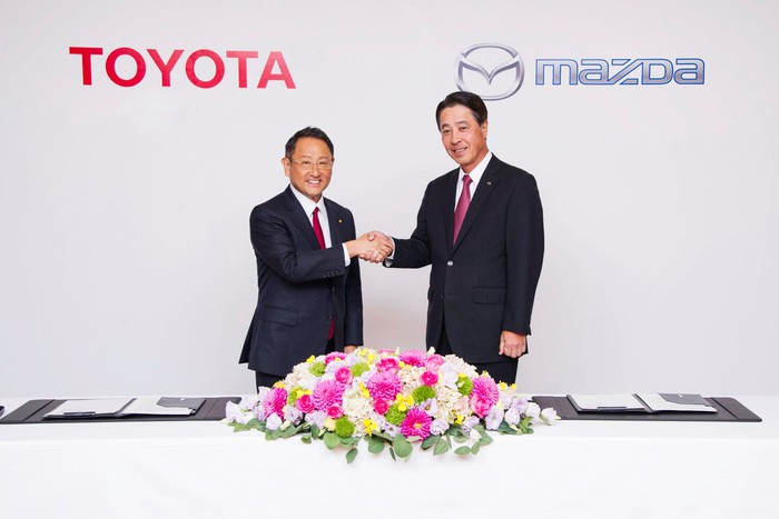 Akio Toyoda and Masamichi Kogai are shown shaking hands before a backdrop with the Toyota and Mazda logos.