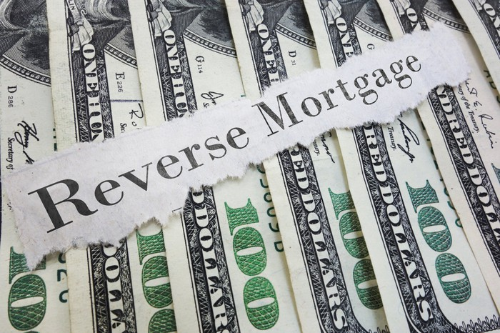"The words ""reverse mortgage"" on a torn piece of paper, on top of hundred dollar bills"