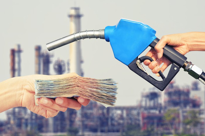 One person's hand holding cash, while another person's hand holds a gas pump. A refinery is out of focus in the background.