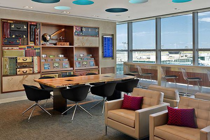 An airport lounge with leather chairs and a long wood table.