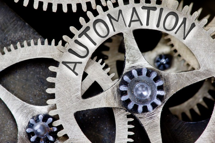 """A gear wheel with """"AUTOMATION"""" carved in it."""