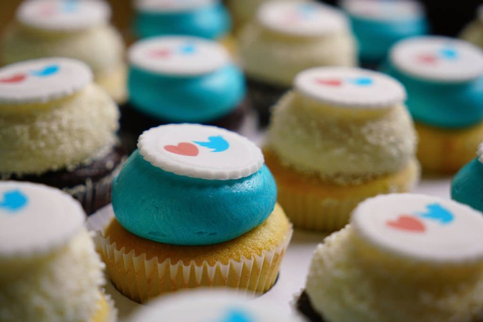 Cupcakes, half with blue frosting, half with white frosting, each under a cookie with a heart and Twitter logo on top.