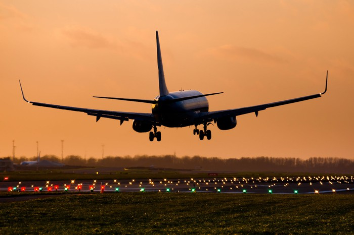 A commercial jet plan lands at sunset.