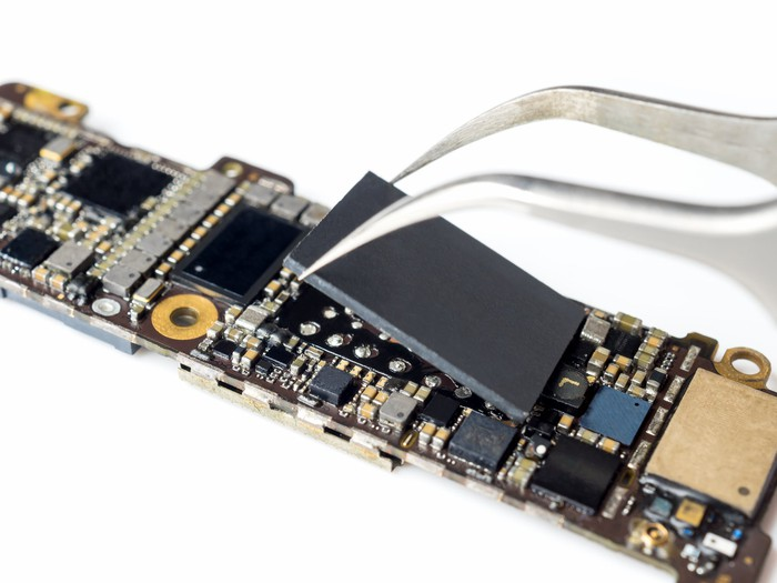 NAND storage chip being installed with tweezers on a smartphone motherboard.