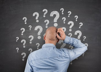 Man scratching head in front of lots of question marks