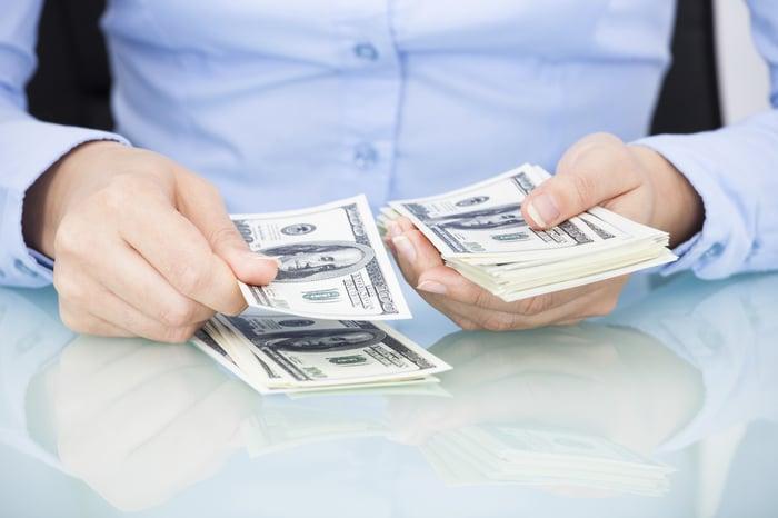 Woman counting hundred dollar bills