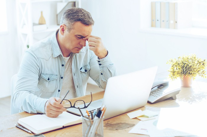 mature man sitting in front of laptop looking stressed out and rubbing bridge of nose