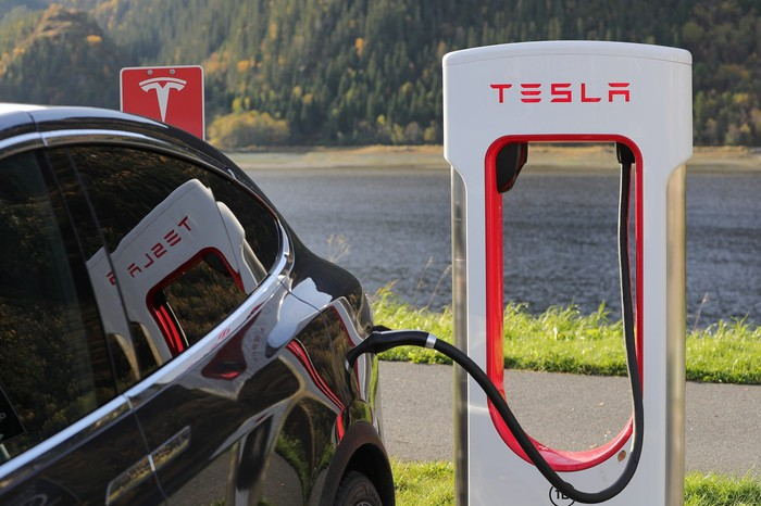 A car is plugged in to a charging unit at a Tesla charging station.