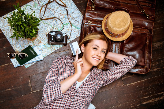 A downward-looking view of a smiling woman holding a credit card, lying on a floor with a suitcase, hat, map, camera, and passport.