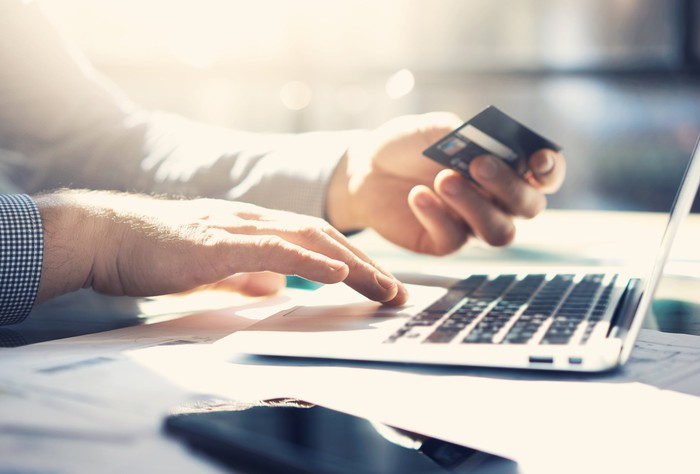 Man sitting in front of a laptop with a bank card in one hand.