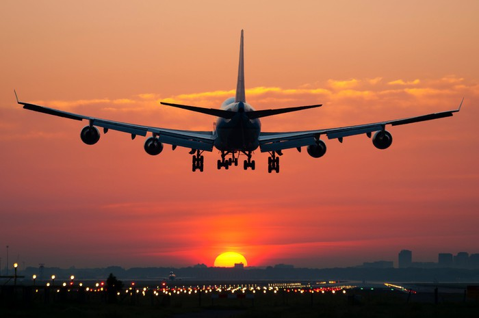 A commercial jet lands on a runway with the setting sun in the background.