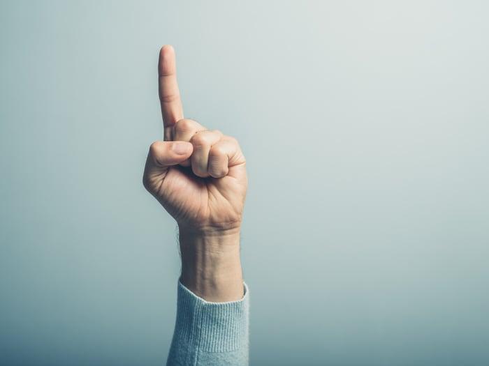 Finger pointing up against blue background