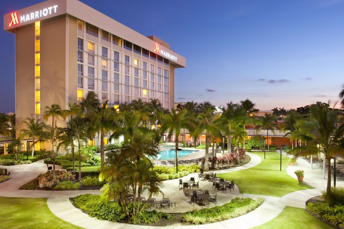 Marriott hotel building with swimming pool and palm tree garden.