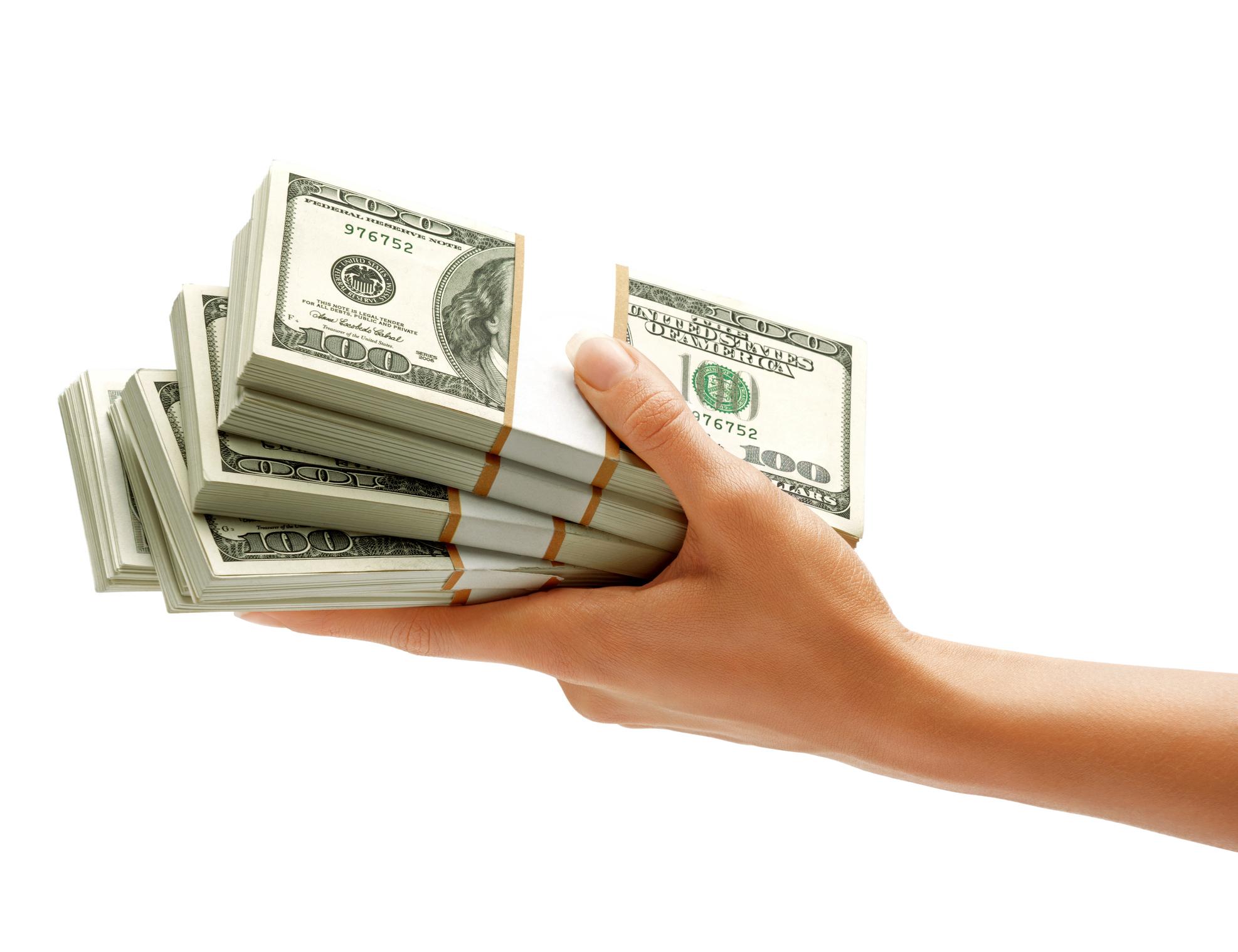 a hand holding a stack of bundles of hundred dollar bills