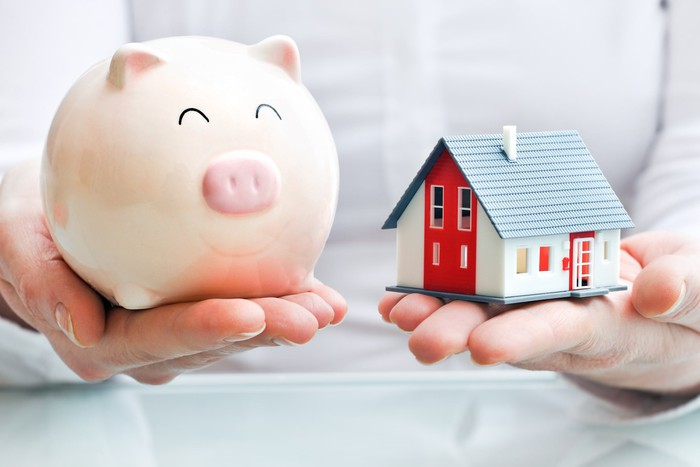 two hands, one holding a piggy bank, one holding a model of a house
