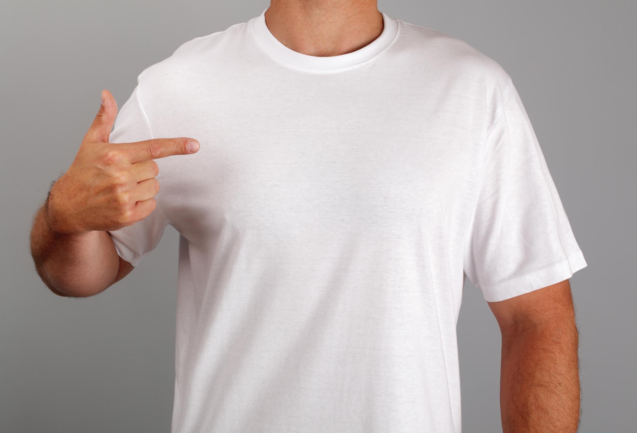 Man wearing white t-shirt pointing at himself.
