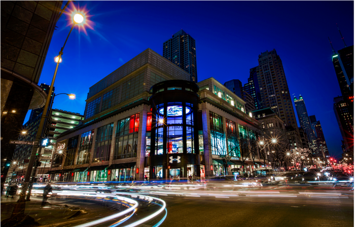 A lighted Under Armour's multi-story store in downtown Chicago at night with time lapse effects of car lights leaving a trail around the corner and across the busy street.