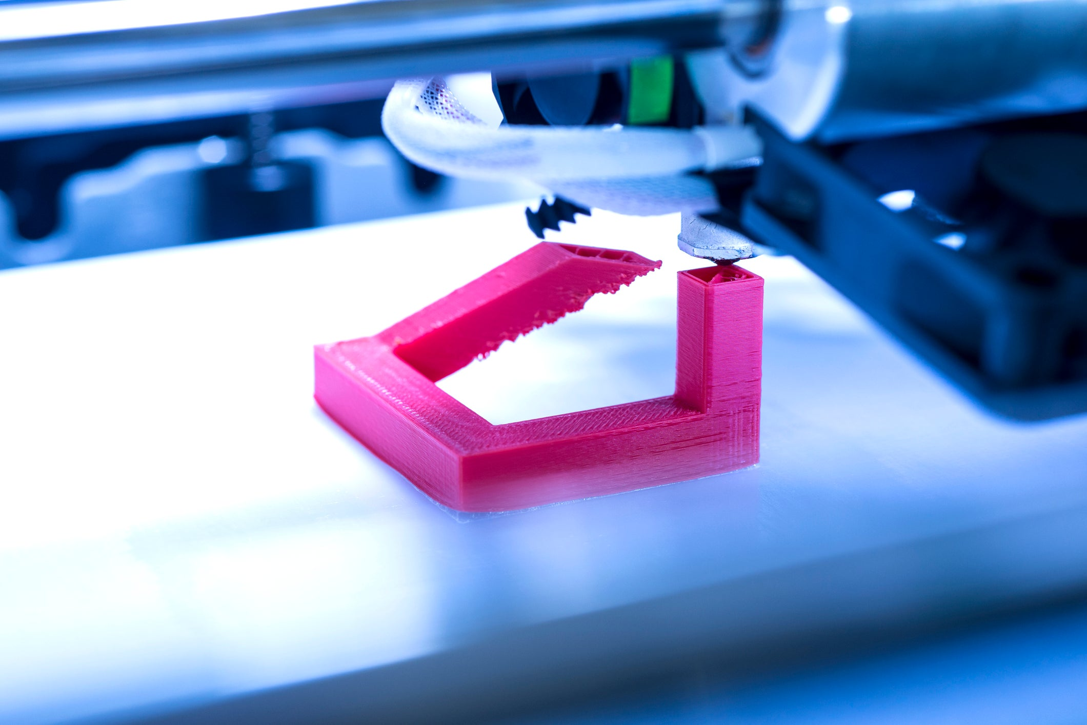 Close-up of a 3D printer printing a fuschia-colored plastic object.