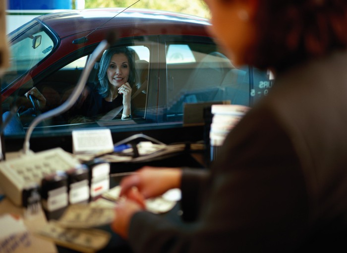 A woman in her car seen from a drive-through teller's booth