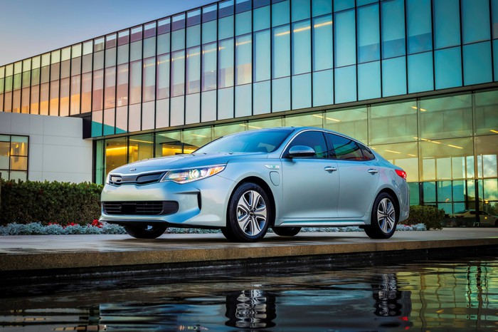 A 2017 Kia Optima Plug-in Hybrid sedan in silver, in front of a glass-paneled office building.