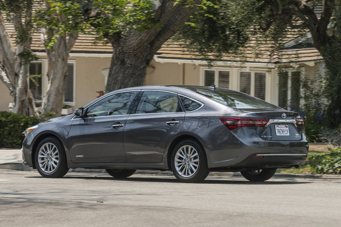 A dark gray 2017 Toyota Avalon Hybrid Sedan parked in front of a house.