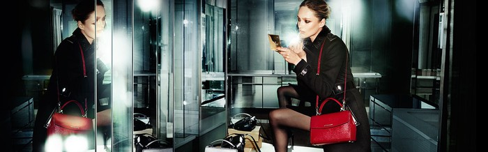 A Michael Kors model looks into refracted mirror holding a makeup kit with a handbag hanging off of her shoulder.