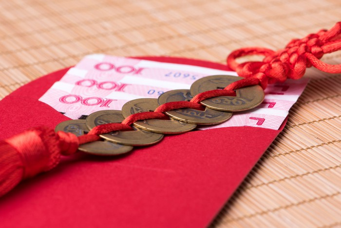 Chinese lucky coins on top of Chinese banknotes inside an open red envelope.