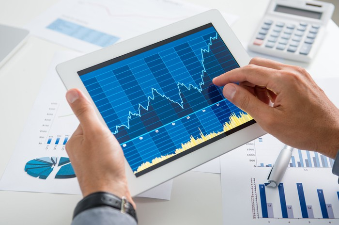 Hands holding a tablet computer showing a rising stock chart, above a table covered in other charts, pens, and a calculator