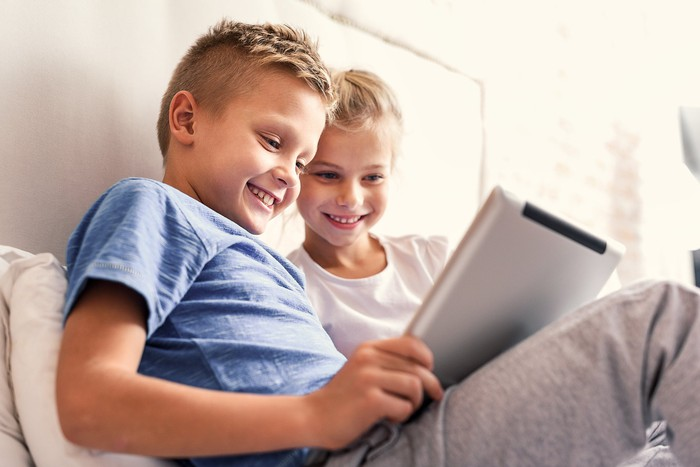 A young boy and girl on a bed, smiling at their tablet screen.