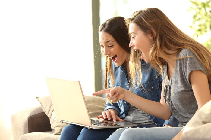 Two young women smiling at something on their laptop screen. One is pointing at the screen.