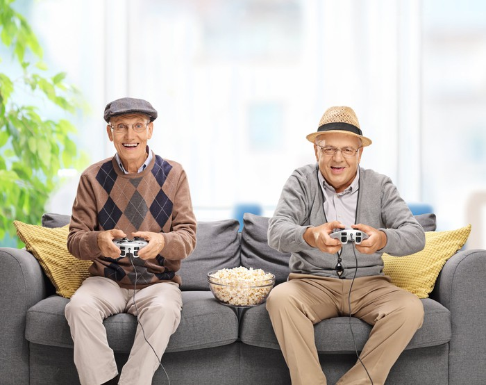 Two senior citizens, smiling, holding video game controllers while sitting on a couch. There is a bowl of popcorn between the men.
