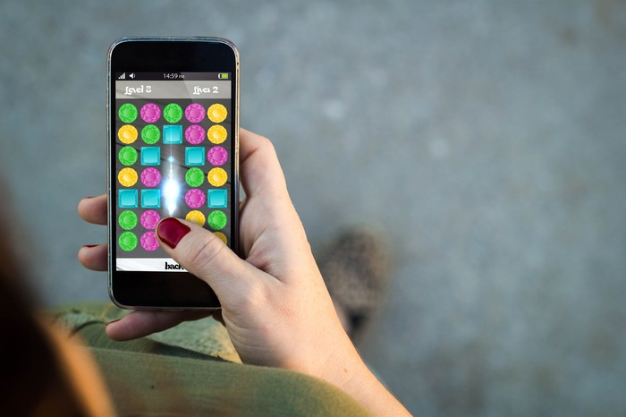 A woman's hand holding a smartphone with a mobile game displayed on the screen.