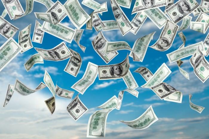 lots of dollar bills raining down from a blue sky
