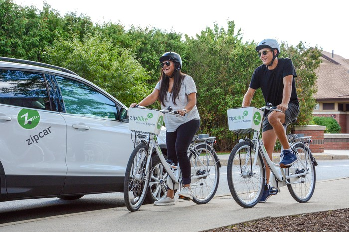 People riding bicycles next to a Zipcar.