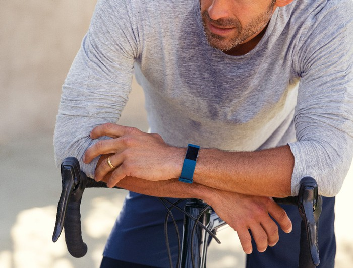 Sweaty guy resting on his bike wearing a Fitbit Charge 2.