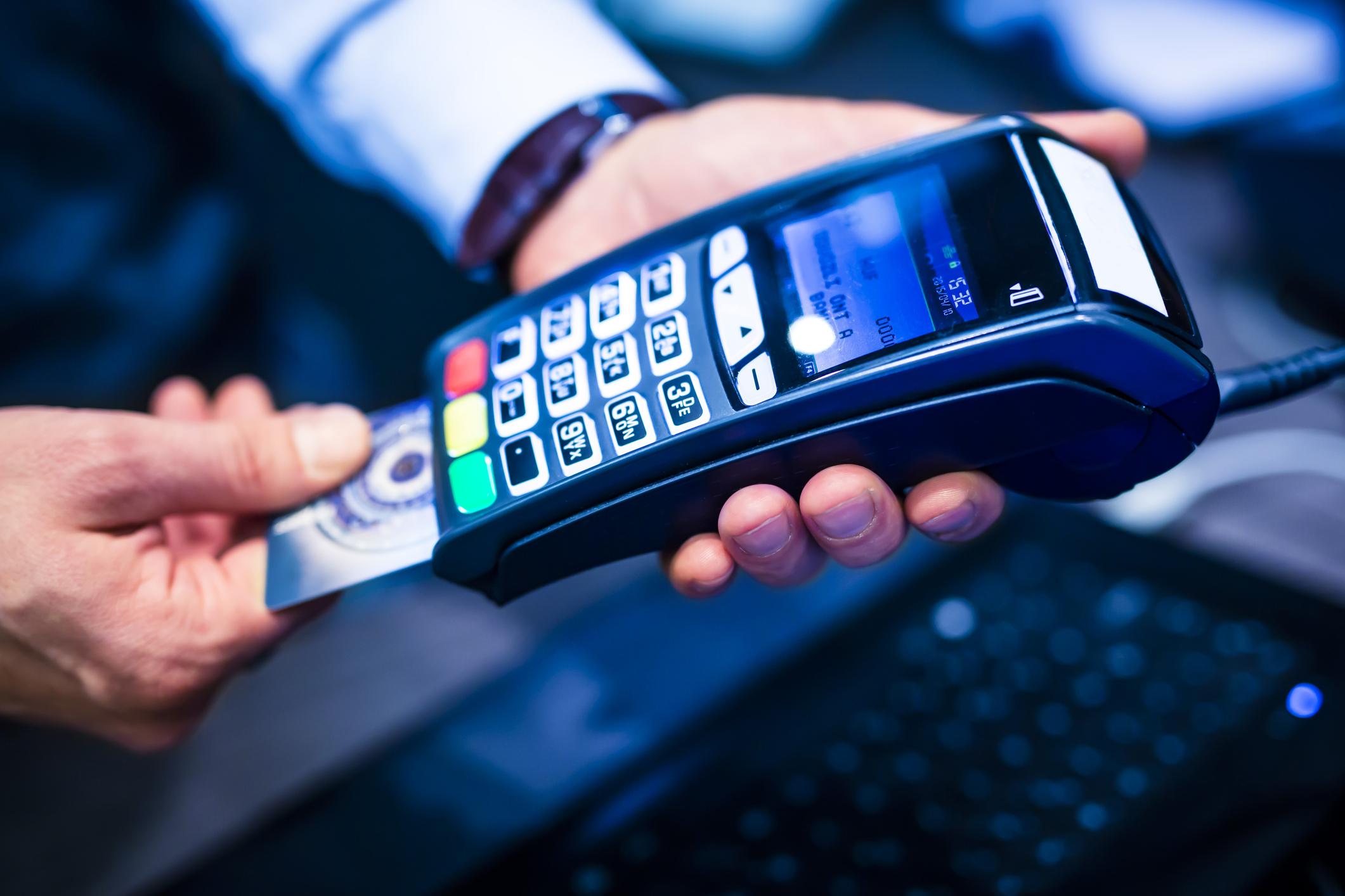 Man inserting a credit card into a handheld credit terminal.