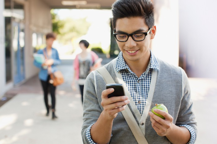 Student with glasses holding a smartphone in one hand.