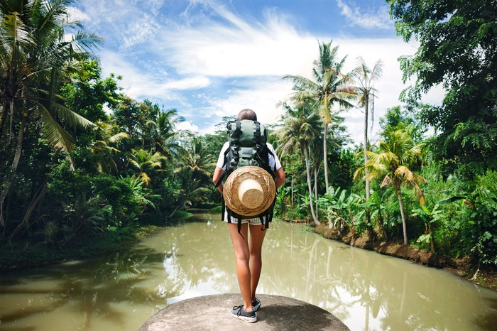 A person wearing a backpack standing on the edge of a muddy lake surrounded by tropical plants.