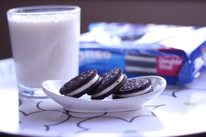 A plate of Oreo cookies and a glass of milk with an Oreo branded package in the background.