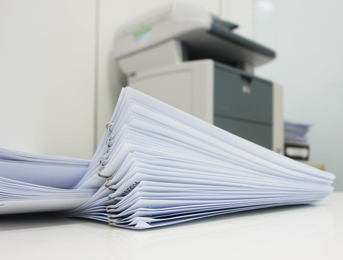 A stack of papers in front of a copy machine.