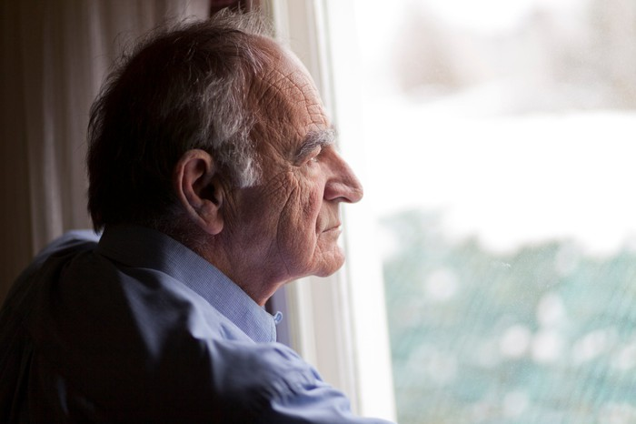 Sad senior man looking out the window